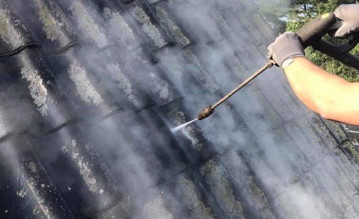 Dakdekker bezig met dak impregneren.